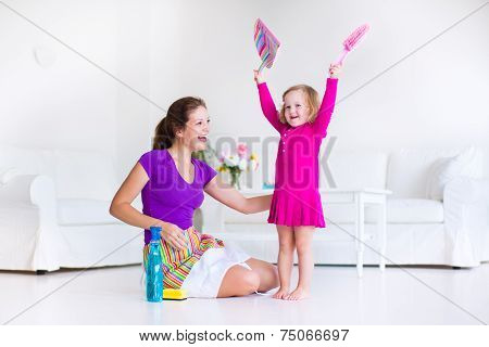 Mother And Daughter Sweeping The Floor