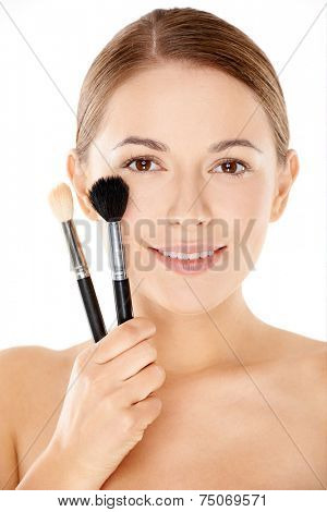 Young woman with a lovely smooth flawless complexion holding a set of cosmetics brushes to her cheek with a smile  beauty concept over white