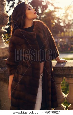 Beautiful Brunette Woman In Luxurious Fur Coat Posing In Autumn Park