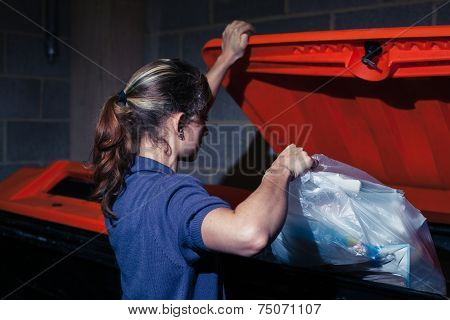 Woman Putting Rubbish In Bin