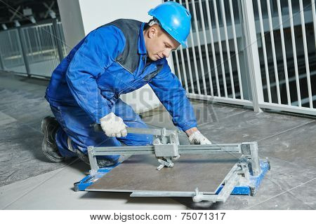industrial tiler builder worker working with floor tile cutting equipment at repair renovation work