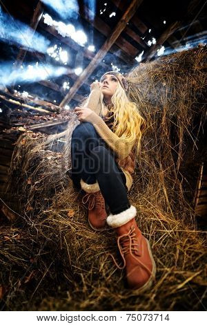 Beautiful woman relaxing in straw in autumn in smoky, dusty room
