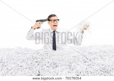 Desperate man holding a gun to his head and standing in a pile of shredded paper isolated on white background