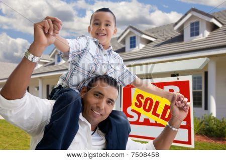 Hispanic Father And Son With Sold Real Estate Sign
