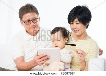 Asian family online shopping indoor, grandparents and grandchild living lifestyle at home.