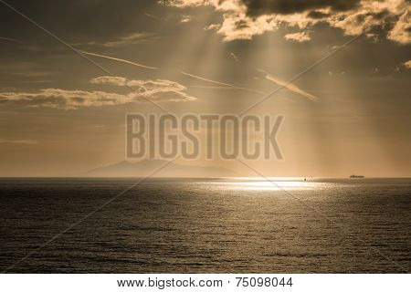 The Sun's Rays On Boats Over The Island Of Elba