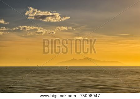Sailing Boats At Sunrise Against A Silhouetted Isle Of Elba