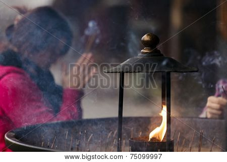 NARA,JAPAN, NOVEMBER 18 : A Japanese woman is praying at the Todai-ji temple in Nara near Kyoto on November 18, 2011 .Shallow depth of field photo with focus on the flame