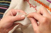 picture of thread-making  - Woman hands sewing process with needle and thread [[** Note: Shallow depth of field] ** Note: Visible grain at 100%, best at smaller sizes - JPG