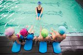 image of swimming  - Cute swimming class watching the coach at the leisure center - JPG