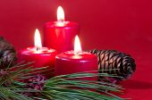 stock photo of pine-needle  - Red Christmas candles burning with pine needles and cones on a red background - JPG