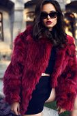 pic of coat  - fashion outdoor photo of beautiful elegant woman with dark hair wearing luxurious red fur coat and sunglasses posing in autumn park - JPG