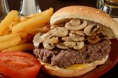 picture of sauteed  - Closeup of a hamburger topped with sauteed mushrooms and bacon with fries - JPG