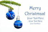 stock photo of merry christmas text  - Closeup of Green Christmas Fir Tree With Two Blue Christmas Balls Whith Silver Decoration On It And Your Text Here White Background Merry Christmas - JPG
