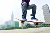 picture of skateboarding  - young  skateboarder legs skateboarding jumping at city - JPG