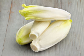 stock photo of endive  - group of belgian endives on wooden table - JPG