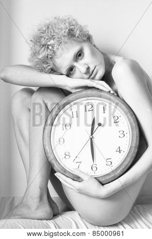 Beautiful young girl with curly hair sitting on the bed with a big clock in his hands. Black and white photography.