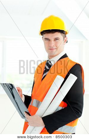 Self-assured Architect Holding A Clipboard And Blueprints