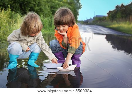 three boy play in puddle summer day