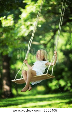Little smiling girl on a swing