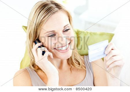 Charming Young Woman Talking On Phone Holding A Card In The Living-room
