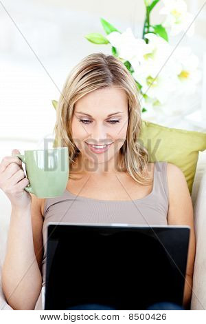 Caucasian Woman Sitting In Front Of Her Laptop And Holding A Cup In The Living-room