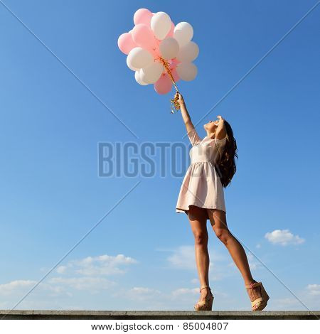 Fashion girl with  air balloons over blue sky