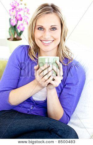 Caucasian Blond Woman Enjoying Her Coffee Sitting On The Sofa
