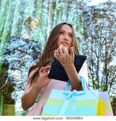 Beautiful young fashion woman holding shopping bags and standing near shop with tablet window
