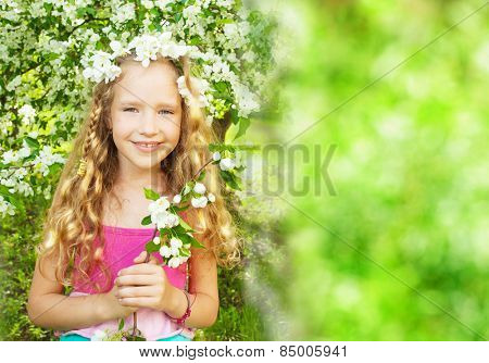 Child at spring. Happy girl outdoors. Blooming apple tree