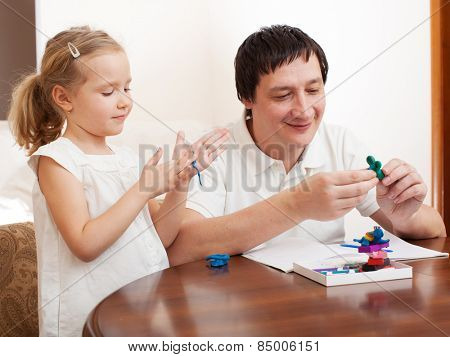 Family molded from clay toys. Father play with girl