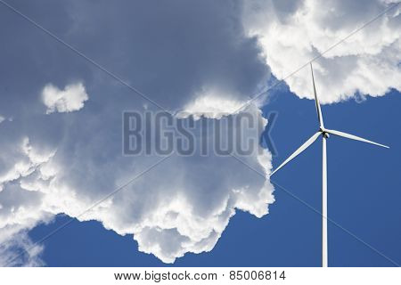 wind power plant set against a clear sky and puffy clouds