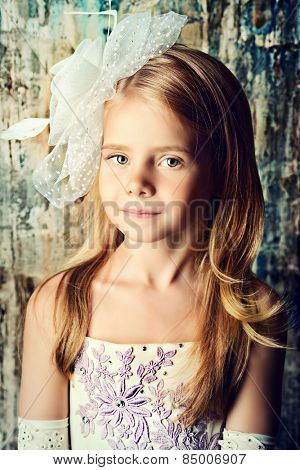 Art portrait of a pretty little girl wearing princess dress and elegant hat. Fashion shot. Childhood.