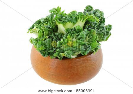 A wooden bowl full of fresh bok choy (Chinese cabbage)