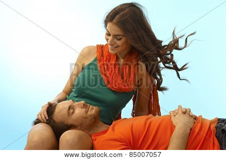 Happy young casual caucasian romantic couple resting with man in lap of girlfriend. Smiling, eyes closed, caressing, relaxing outdoor. Copyspace.