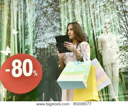 Beautiful young fashion woman holding shopping bags and standing near shop with tablet window, toned