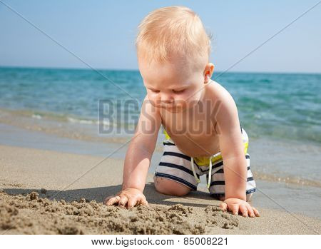 10 month baby boy wearing swimming shorts playing on a beach