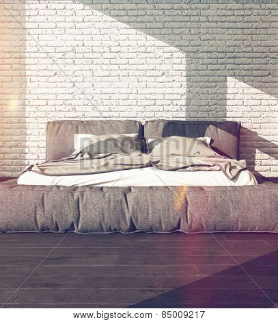Close up of a large king size bed in a sunny bedroom with rumpled bed linen against a textured white brick wall, neutral tones with flare effect. 3d Rendering.