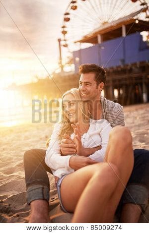 couple sitting in the sand on the beach near santa monica pier in california usa at sunset with bright golden lens flare
