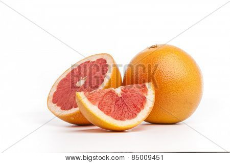 Slices of grapefruit along with whole fruit.