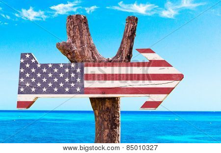 United States Flag wooden sign with a beach on background