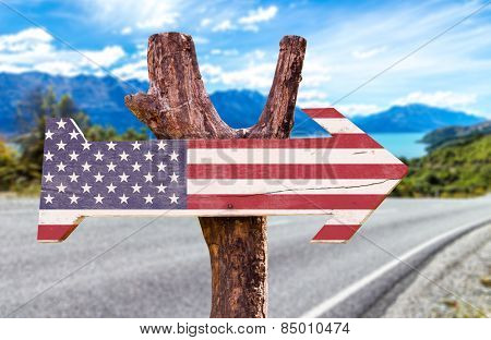 United States Flag wooden sign with a road background