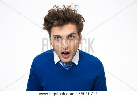 Surprised young man looking at the camera over white background
