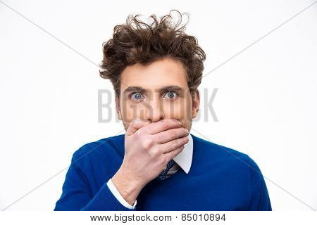 Portrait of a young man covering his mouth over white background