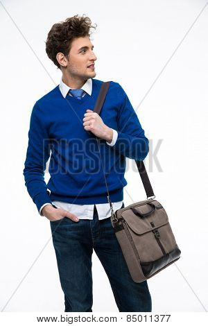 Happy young business man with bag looking away over gray background