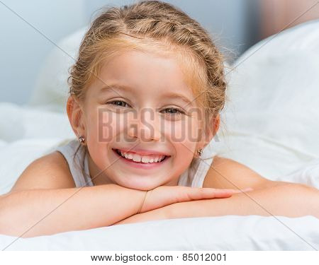 cute smiling little girl woke up in white bed