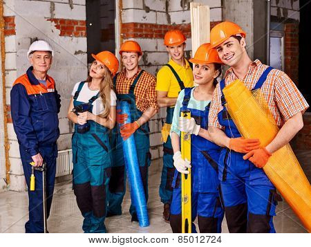 Happy group people in builder uniform. Senior man.