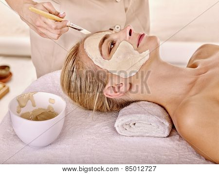 Woman with clay facial mask in beauty spa. Isolated. Plate on table