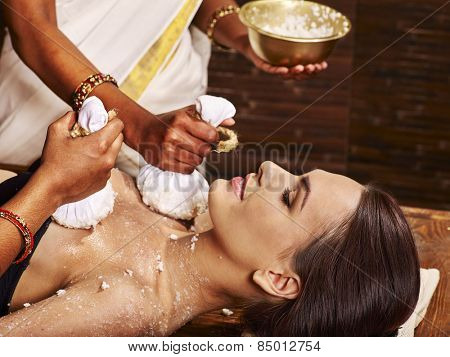 Woman having ayurvedic massage with pouch of rice. Close up.