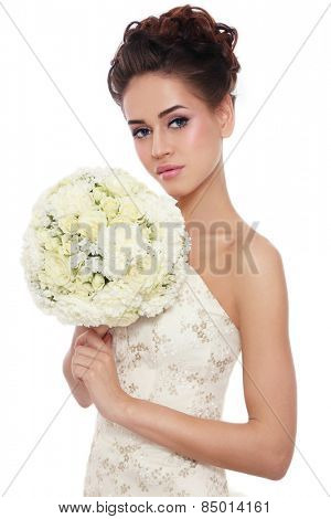Young beautiful slim bride with stylish make-up and hairdo holding bouquet in her hand over white background